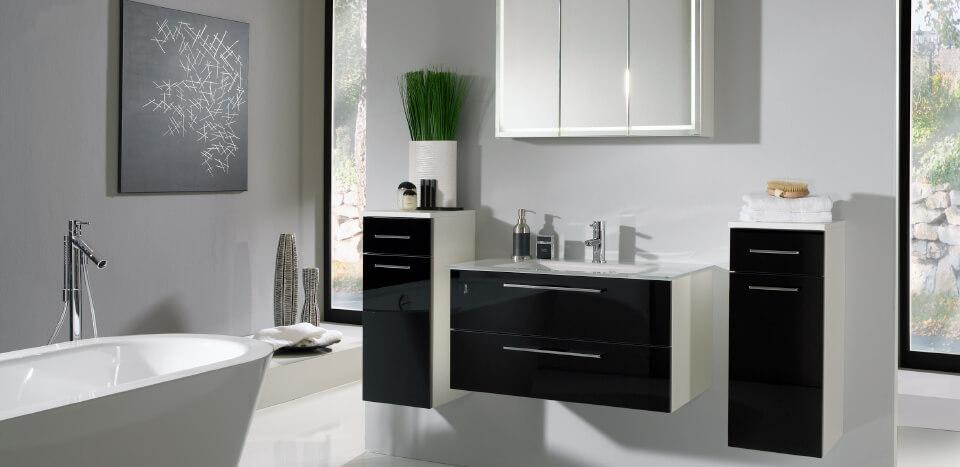 Black and white interior designed bathroom with a ceramic bathtub
