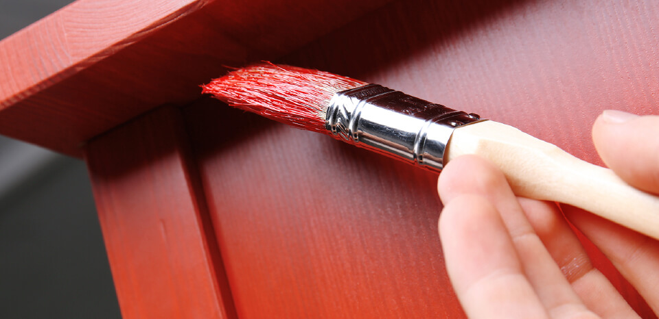 Furniture being painted with red paint