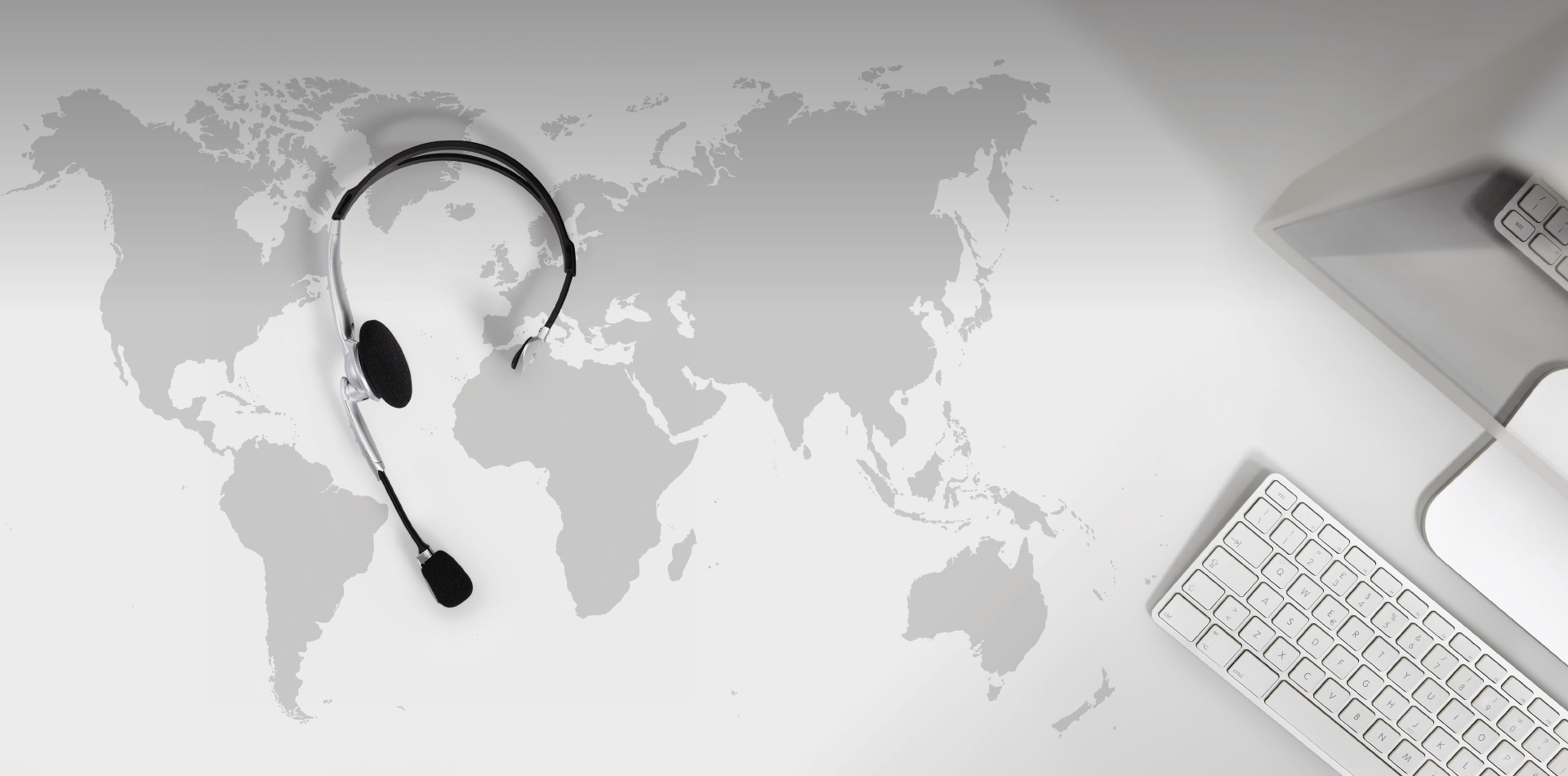 Headphones and a keyboard on top of a world map