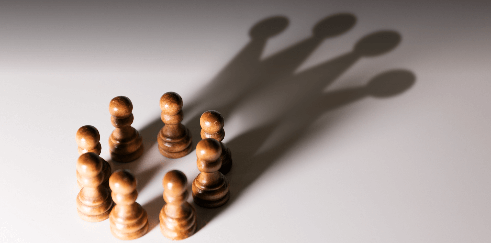 A group of pawns shadows creating a crown