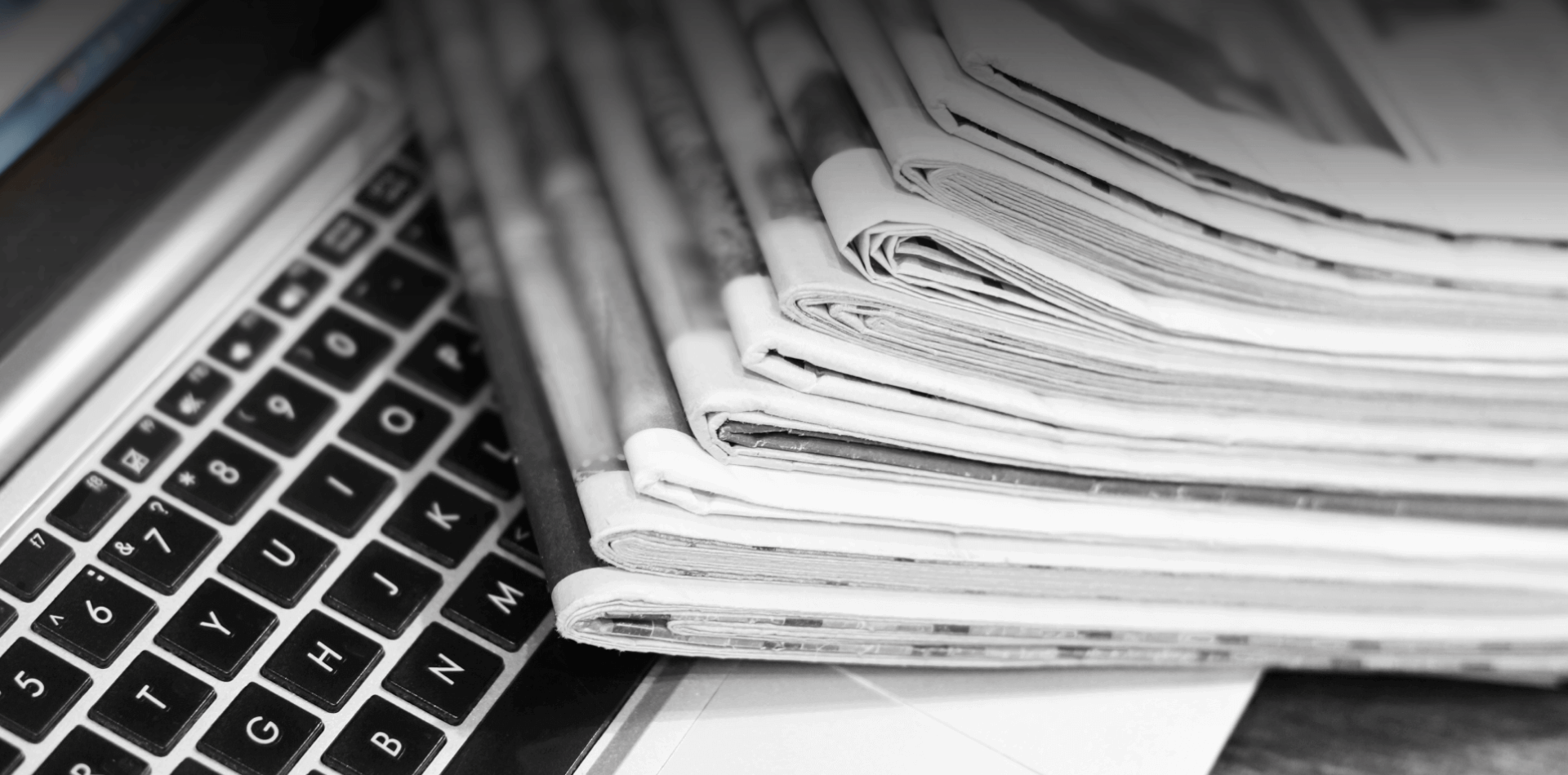 Newspapers on top of a laptop