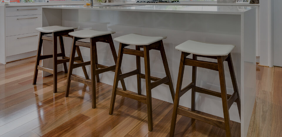 A kitchen with wooden chairs and wooden flooring